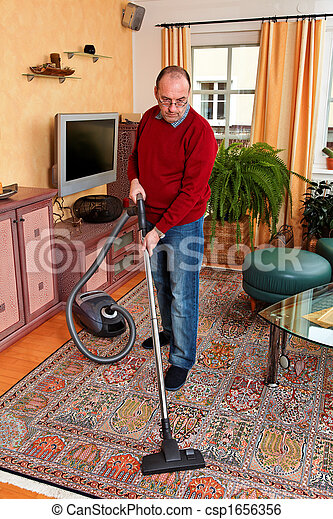 Man at home with a vacuum cleaner - csp1656356