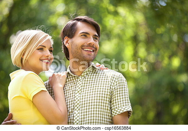 Loving couple in park. Happy young couple standing close to each other and smiling - csp16563884