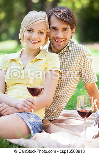 Date in park. Happy young couple drinking wine on a picnic - csp16563918