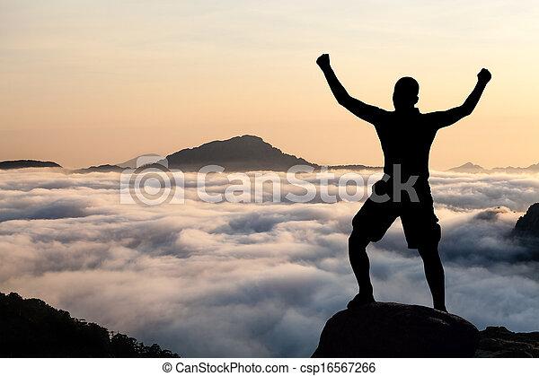 Man hiking climbing silhouette in mountains - csp16567266