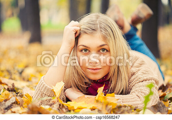 young woman laying down on the ground in autumn park - csp16568247