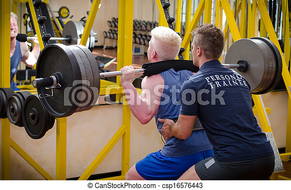 Personal trainer helping client in gym - csp16576443