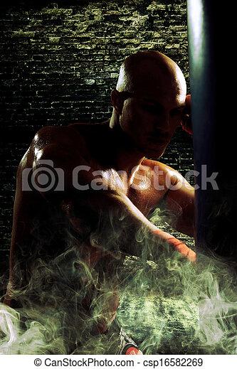 boxer man during boxing hiting heavy bag at training fitness - csp16582269