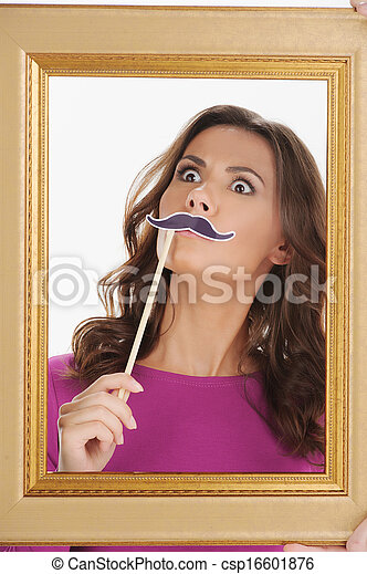 Making a face. Beautiful young women looking through picture frame and holding a face moustache in front of her face while isolated on white - csp16601876