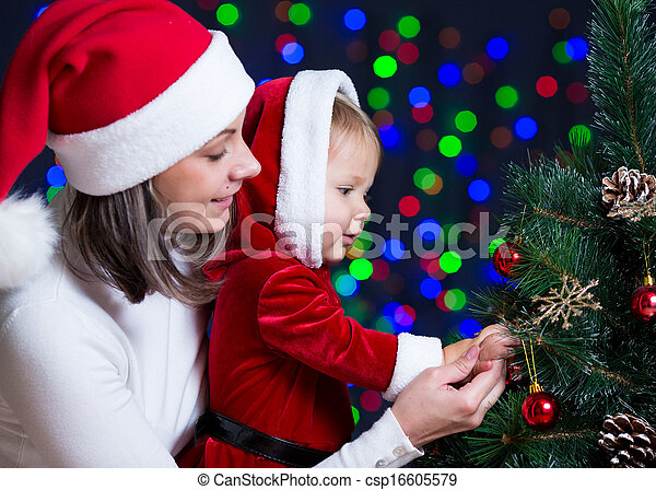 baby girl with mother decorating Christmas tree on bright background - csp16605579