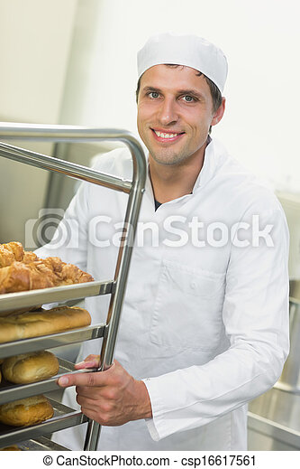 Young baker pushing a trolley with food on it - csp16617561