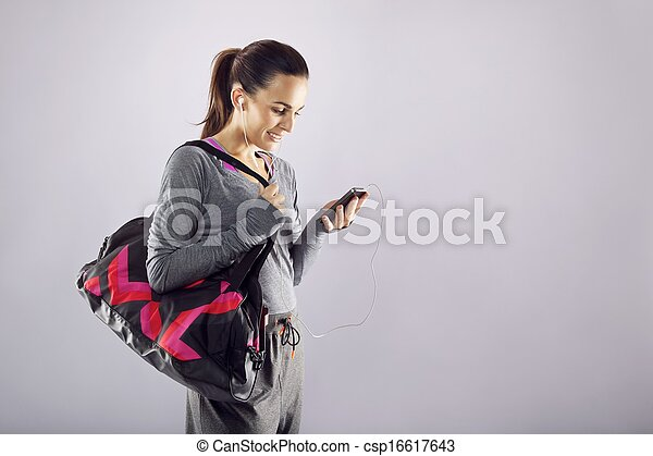 Fitness woman with gym bag listening music - csp16617643