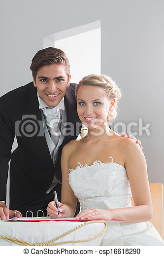 Young married couple sitting at table signing wedding register