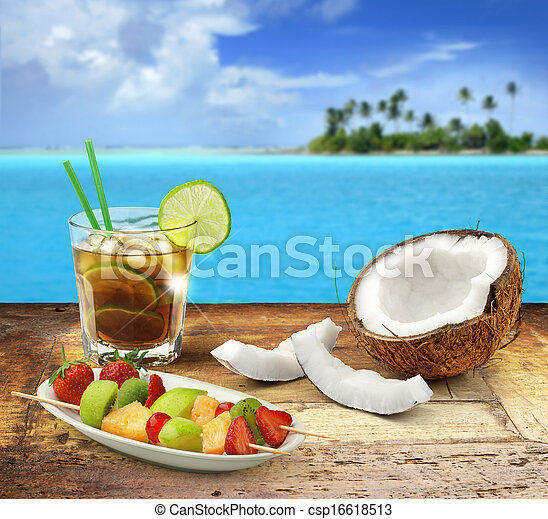 cuba libre and tropical fruit on a wooden table in a polynesian seascape - csp16618513