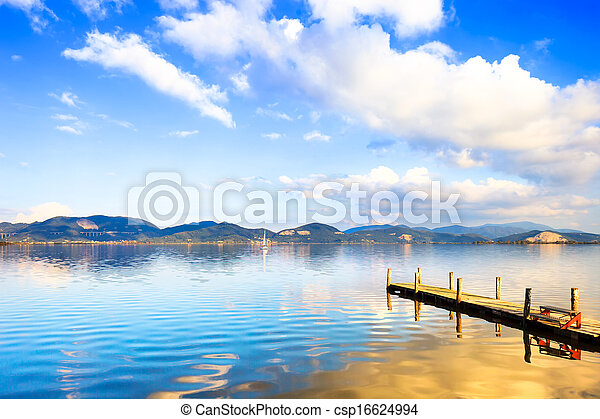 Wooden pier or jetty and on a blue lake sunset and sky reflection on water. Versilia Tuscany, Italy - csp16624994