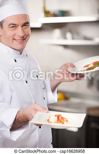 Confident chef. Cheerful chef holding plates with food and smiling - csp16626958