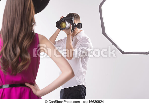 Photographer and model. Young man photographing fashion model holding hands on hip - csp16630924