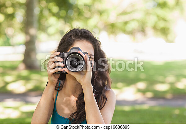 Front view of cute brunette woman taking a picture with her camera in a park - csp16636893