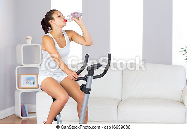 Lovely slender woman drinking while training on an exercise bike in her living room at home - csp16639086