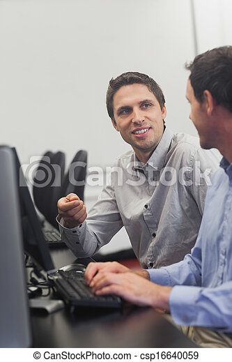 Two friendly men talking sitting in front of a computer - csp16640059