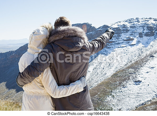 Rear view of a loving couple in fur hood jackets looking at snowed mountain range - csp16643438