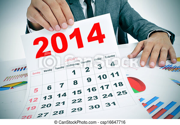man in suit with charts and a 2014 calendar - csp16647716