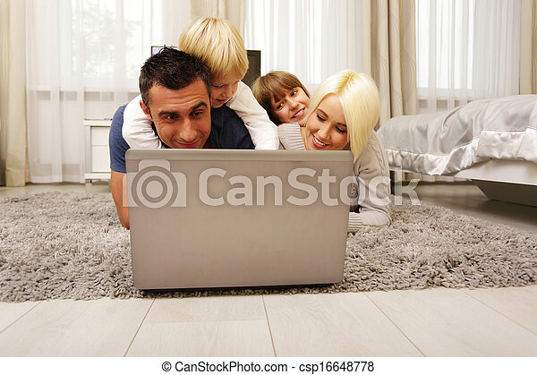 happy family lying on the carpet and playing on a laptop at home