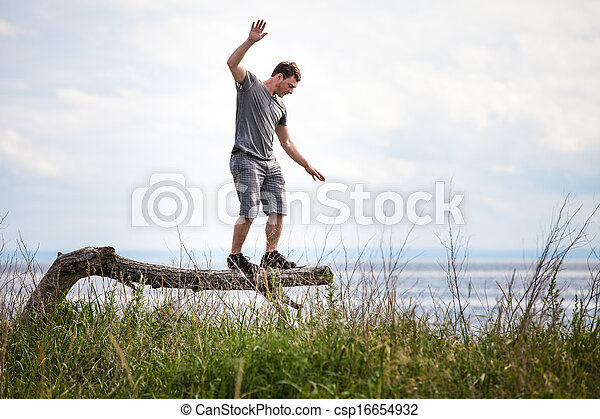 Young Adult Balancing on a Tree in Vacation - csp16654932