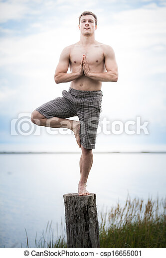 Young Adult Doing Yoga on a Stump in Nature - csp16655001