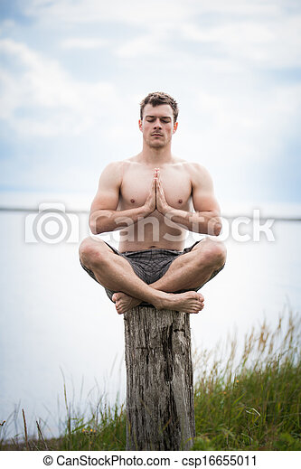 Young Adult Doing Yoga on a Stump in Nature - csp16655011