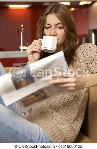 mid adult woman drinking coffee and reading news - csp16680122