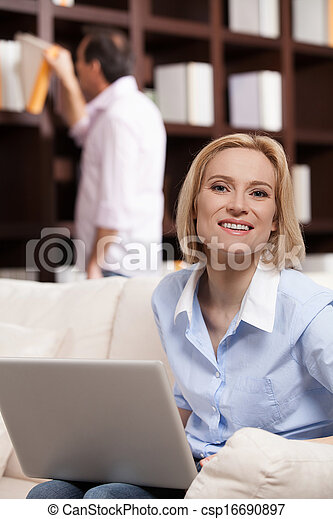Happy woman. Cheerful middle aged woman working at the computer and smiling while her husband choosing a book to read at the background - csp16690897