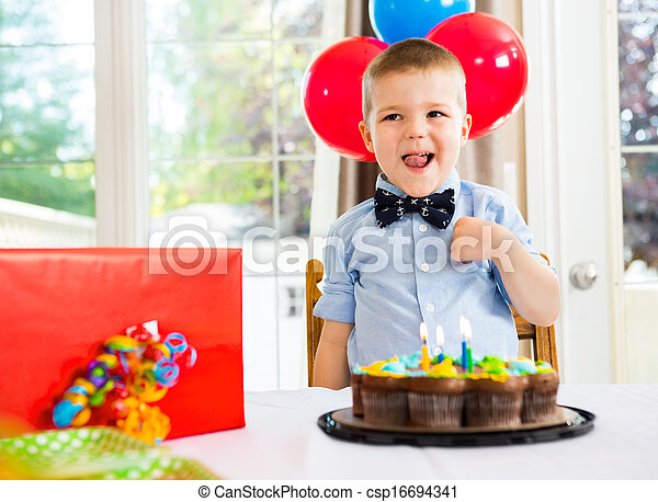 Birthday Boy With Cake And Present On Table - csp16694341