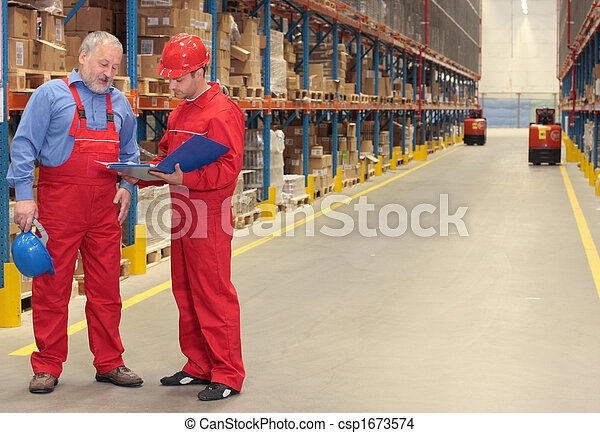 two workers in uniforms in warehouse - csp1673574