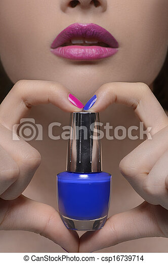 Choose your color. Close-up cropped image of beautiful women holding a nail polish with her fingers