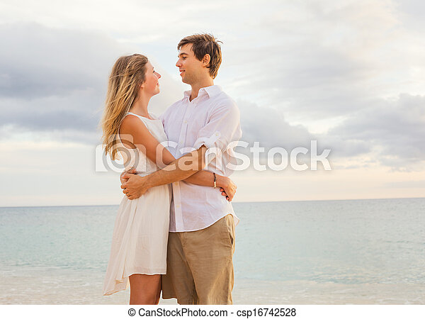 Happy romantic couple on the beach at sunset embracing each other. Man and woman in love watching the sun set into ocean - csp16742528