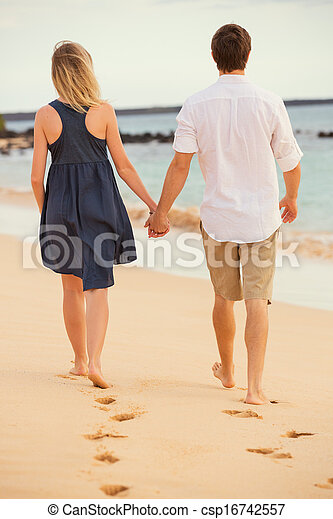 Romantic happy couple walking on beach at sunset. Smiling holding hands. Man and woman in love - csp16742557