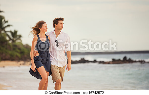 Romantic happy couple walking on beach at sunset. Smiling with arms around each other. Man and woman in love - csp16742572