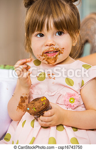 Girl Eating Birthday Cake With Icing On Her Face - csp16743750