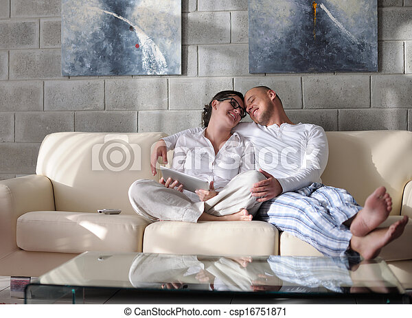young couple using tablet computer at home - csp16751871