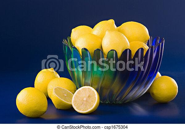lemons in blue green bowl on blue background - csp1675304