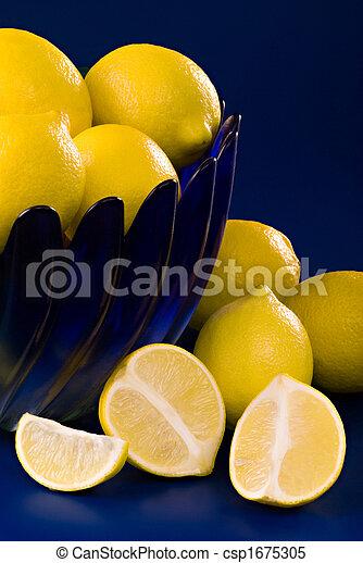 lemons in blue bowl on blue background - csp1675305