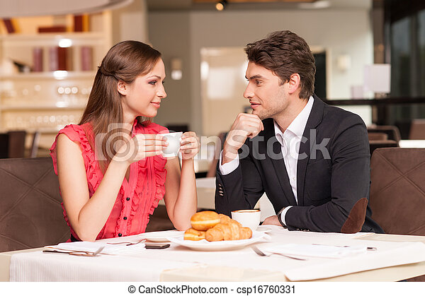 Loving couple having romantic breakfast at the restaurant. Looking at each other and smiling.  - csp16760331
