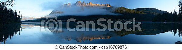 Panoramic image Lucerne Peak lit by the rising sun reflected in calm waters of Yellowhead Lake on early summer morning. The lake is located in Mount Robson Provincial Park, British Columbia, Canada. - csp16769876
