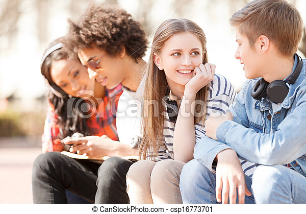 Teenage friends. Four cheerful teenage friends talking to each other