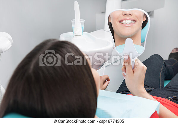 Patient at dentist office. Rear view of cheerful young woman sitting at the chair in dental office and looking at the mirror - csp16774305