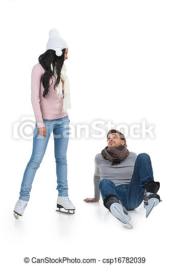 Mixed race couple skating at the skating rink. Man falling down while African girl teaching - csp16782039