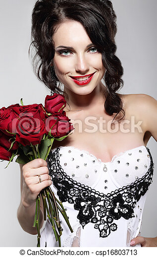 Fragrance. Beautiful Young Woman Holding Bouquet of Red Roses. Valentine's Day - csp16803713
