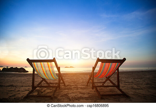 Pair of beach loungers on the deserted coast sea at sunrise, perfect vacation concept. - csp16806895