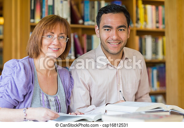 Adult students studying together in the library - csp16812531