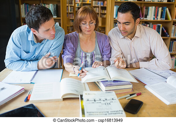 Adult students studying together in the library - csp16813949