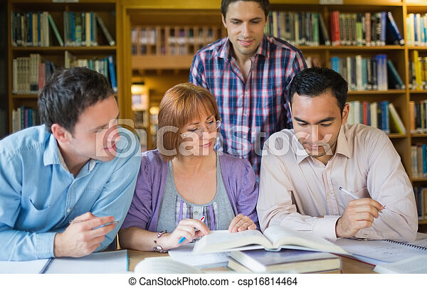 Adult students studying together in the library - csp16814464