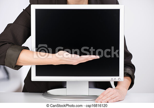 Woman pointing to a blank computer monitor - csp16816120