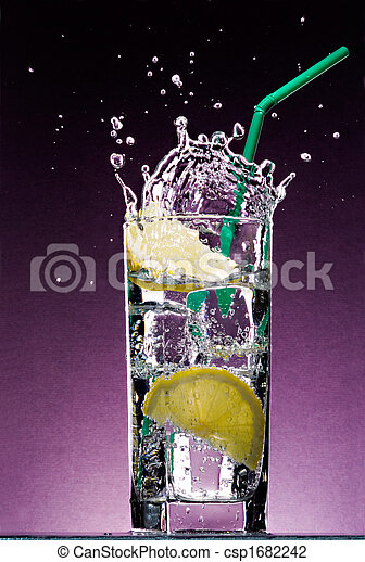 sliced lemon falling in glass of alcoholic drink with ice cubes and green straw on textured violet background - csp1682242