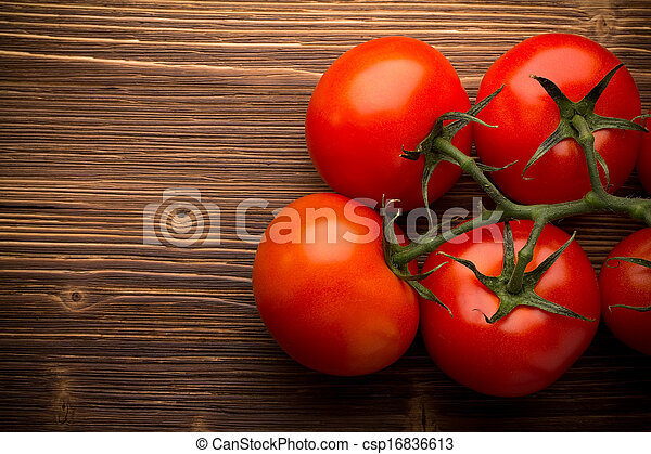 Tomato bunch on a wooden background.